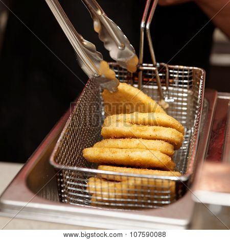 Chef is cooking nuggets in a deep fryer