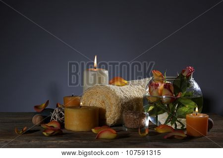 Beautiful spa composition with alight candles on wooden table