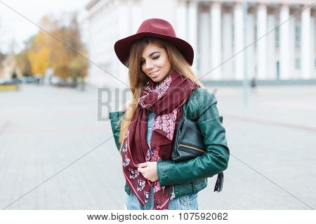 Beautiful Girl Smiling In A Fashionable Hat And Scarf On The Background Of The City