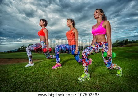 Bright beautiful young girls doing sports with dumbbells