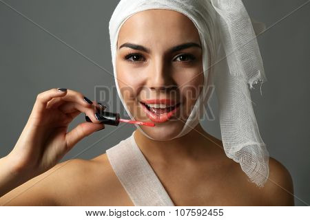 Young emotional woman with a gauze bandage on her head and chest, holding lip gloss, on grey background