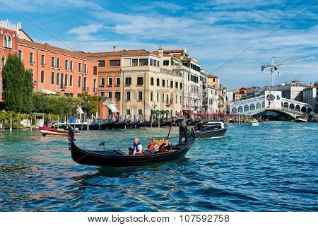 VENICE, ITALY - 17 OCTOBER 2015: Tourists on a gondola on the Grand Canal in Venice with the Rialto bridge in the background in a travel and tourism concept. Venice, Italy. October 17 2015.
