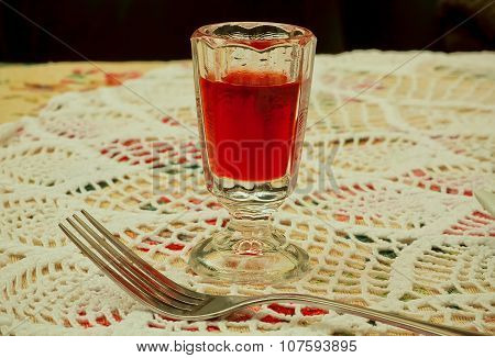 Glass With Liquor And Fork On The Tablecloth