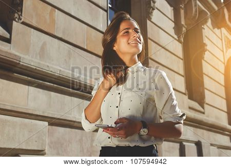 Fancy hipster girl is using smart phone street look of female model with mobile phone