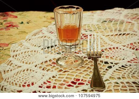 Orange Aperitif In A Crystal Glass On The Retro Tablecloth