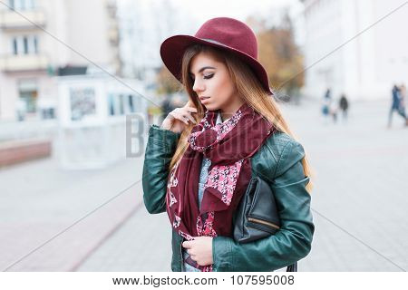 Beautiful Girl In A Hat, Scarf And Jacket On The Background Of The City Bustle