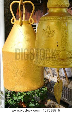 Close up of two golden bells in temple, different styles, bigger one in sunlight