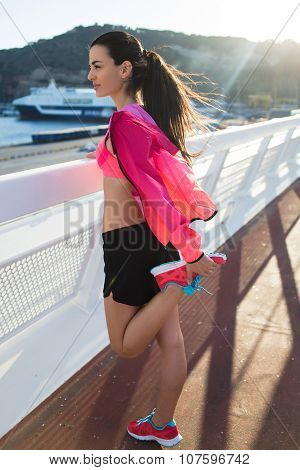 Young healthy fit woman with perfect slender body doing stretching exercises for legs