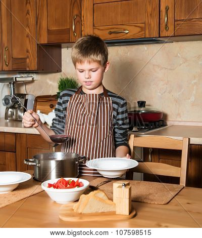 Boy serving Borshch, traditional Russian and Ukrainian soup. Pouring soup into a plate with ladle fr