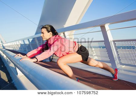 Healthy woman jogger stretching legs before began her run in the fresh air