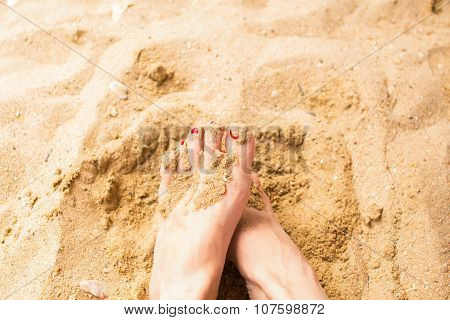 woman feet on the sand in the beach