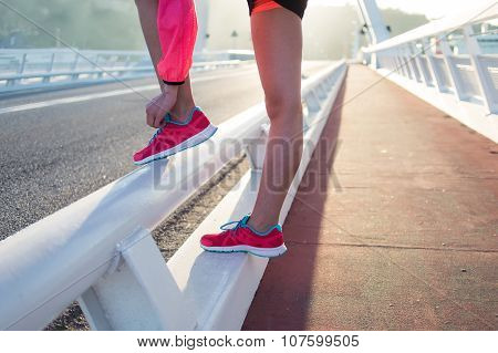 Young athletic woman tie shoelaces while taking break between workout outdoors