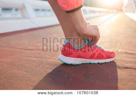 Athletic female tying the laces on running shoes while taking break between training outside