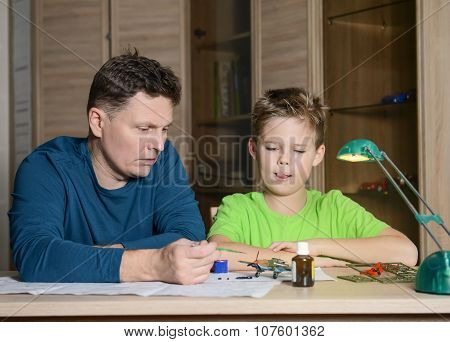 Hobby and family concept. Creating model plane. Happy son and his father are making aircraft mode