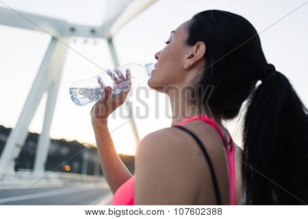 Athletic woman relaxing after active evening jog in the fresh air
