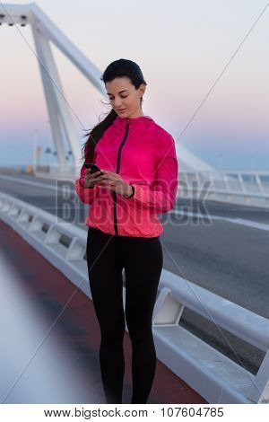 Young athletic woman reading message on cell telephone during break between workout