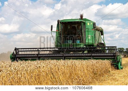 Combine harvests wheat on a field in sunny summer day