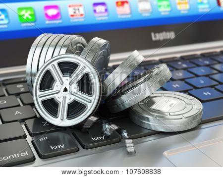 Video or movie online internet concept. Film reels on laptop keyboard. 3d