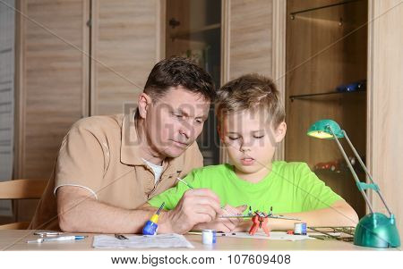 Creating the model plane. Happy son and his father are making aircraft model. Hobby and family conce