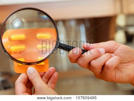 Woman Inspecting Pills With Magnifying Glass.