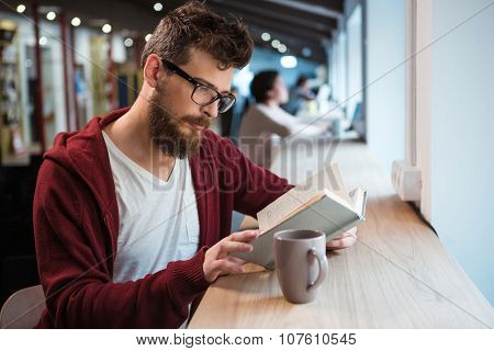 Clever serrious handsome boy in glasses and brown hoodie reading a book sitting at the desk
