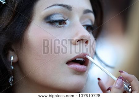 A Young Girl Paints Her Lips