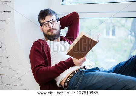 Student with beard in glasses sitting on window sill and reading