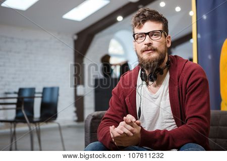 Hipster with beard in glasses and in brown hoodie sitting on sofa in the hall