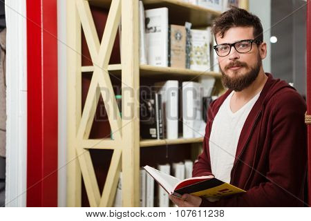 Handsome boy with beard in brown hoodie and glasses reading book