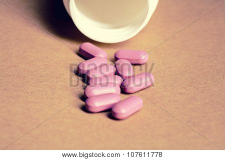 Pills spilled from a bottle on craft paper background front vie