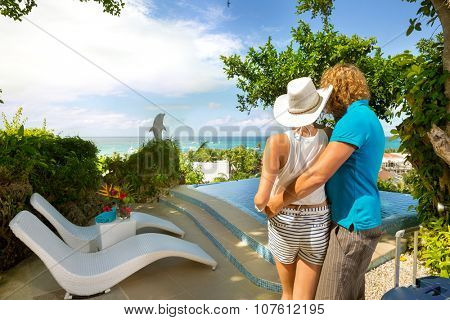 Back view of  tourists on summer vacation, couple with suitcase looking in luxury resort