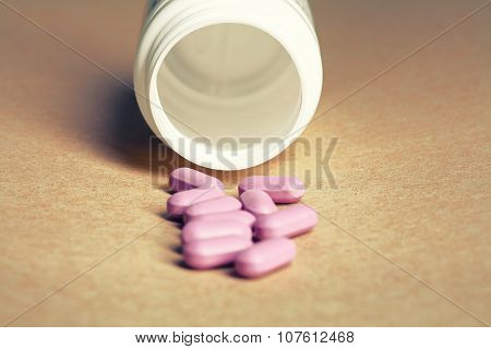 Violet pills spilled from a bottle on a craft paper background front view.