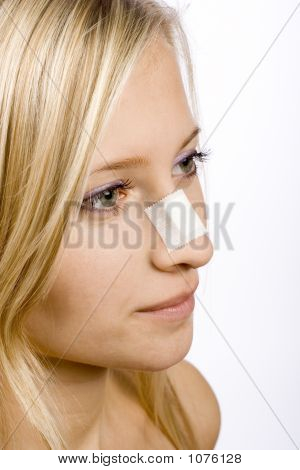 Face Of Young Woman With Sticking Plaster On Nose