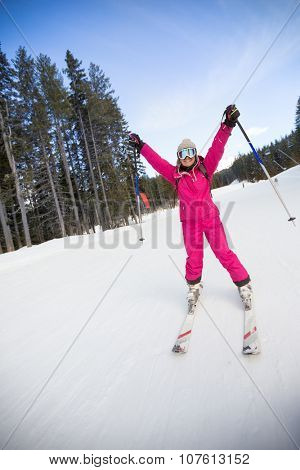 Young happy woman skier with hands up on slope