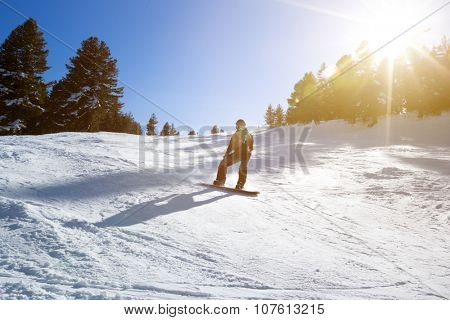 Young snowboarder man on the slope, male snowboarder on the slopes on a sunny morning in the Bansko, Bulgaria