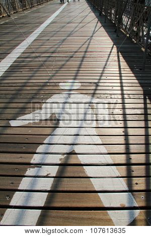 Pathway sign on Brooklyn Bridge with morning sunlight and shadow from cable lines