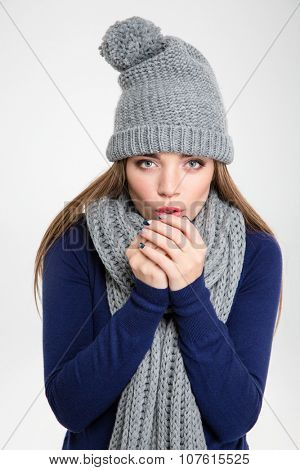 Portrait of a beautiful woman blowing in her hands when feeling cold isolated on a white background