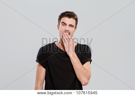 Exhausted young handsome sleepy guy yawning and closing mouth by hand