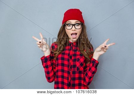 Portrait of a cheerful trendy woman showing two fingers sign over gray background