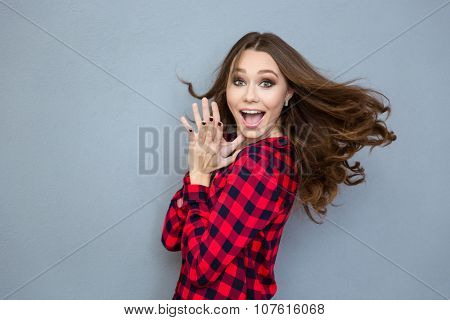 Portrait of a cheerful woman looking at camera over gray background