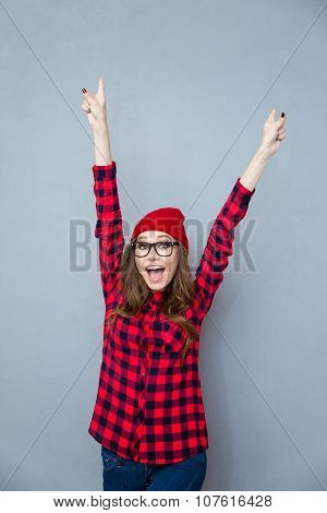 Portrait of a cheerful woman standing with raised hands up over gray background and looking at camera