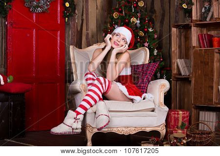 Beautiful Santa girl dreaming near the Christmas tree, making a wish. Vintage new year atmosphere