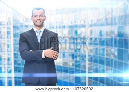 Portrait of business man with hands crossed on blue background. Concept of leadership and success