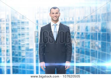 Portrait of smiling businessman, modern background. Concept of leadership and success