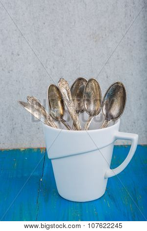 Bunch Of Silver Teaspoons In A White Cup