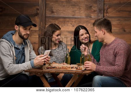 Happy friends communicating while one man looking at his mobile phone