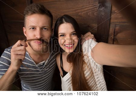 Happy couple making selfies isolated on wooden background