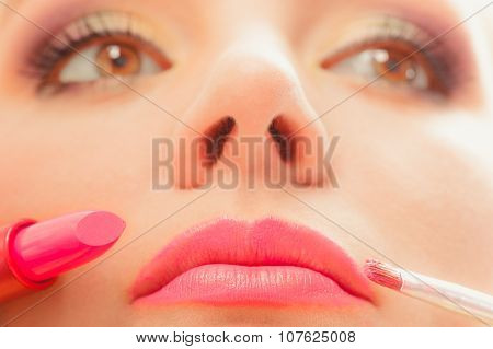 Woman Applying Lipstick With Brush On Lips. Makeup