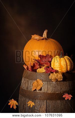 Pumpkins sitting on rustic wooden barrel with fall leaves