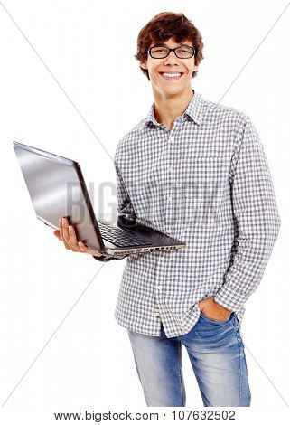 Young hispanic man wearing checkered shirt, blue jeans and black glasses holding open laptop in his hand and smiling isolated on white background - information technology concept